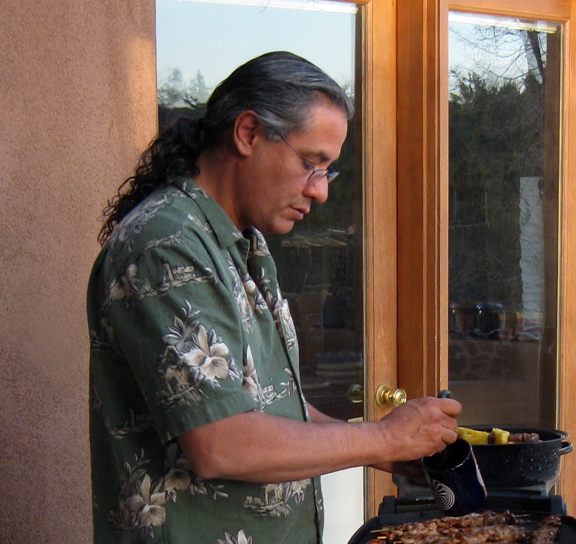 Man in a green short-sleeved button up and glasses cooking meat on a grill