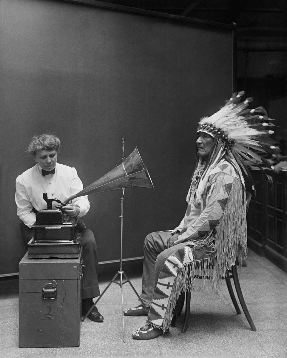 Black and white photograph of a man in traditional Blackfoot clothing and war bonnet being recorded by a woman in Edwardian clothing